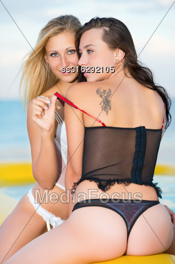 Two Playful Women In Lingerie Posing On The Beach Stock Photo