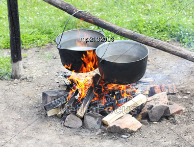 Two Pot Hanging Over The Fire. Preparing Food On Campfire In Wild Camping Stock Photo