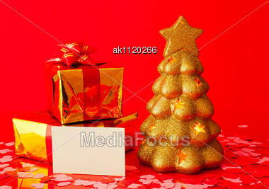 Two Presents, Blank Card And Golden Evergreen Tree Over Red Background Stock Photo