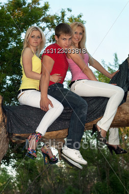 Two Pretty Blonde And Young Man Sitting On A Tree Branch Stock Photo