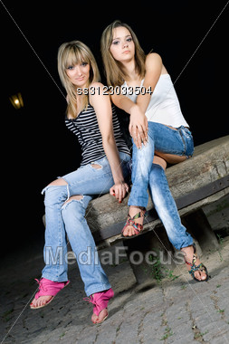 Two Pretty Girls Sitting On A Stone Bench Stock Photo