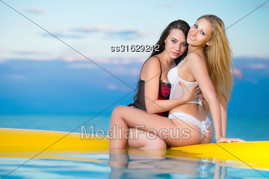 Two Sexy Women In Underwear Posing On The Yellow Pool At Sunset Stock Photo