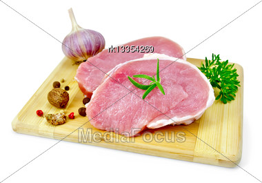 Two Slices Of Pork, Garlic, Nutmeg, Parsley, Rosemary And Pepper On A Wooden Board Isolated On White Background Stock Photo