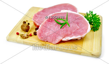 Two Slices Of Pork, Nutmeg, Parsley, Rosemary And Pepper On A Wooden Board Isolated On White Background Stock Photo