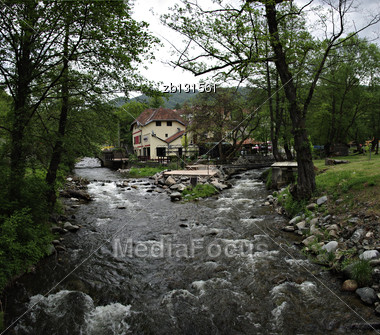 Two Small Creeks Making A Small River In Front Of Countryside House Surrounded With Green Trees Stock Photo