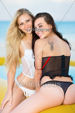 Two Smiling Women In Underwear Posing On The Yellow Pool Stock Photo