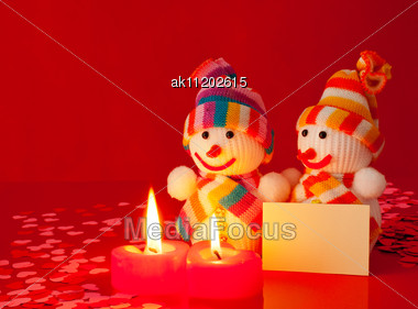 Two Snowmen With Two Burning Heart Shaped Candles Stock Photo