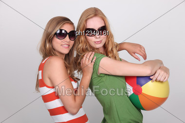 Two Teenagers Wearing Sunglasses Holding Beach Ball Stock Photo
