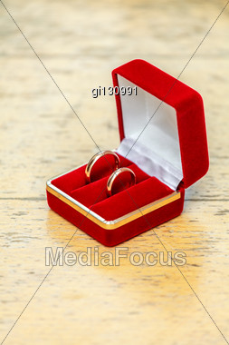 Two Wedding Rings In A Box Of Red, Lying On A Wooden Table Stock Photo