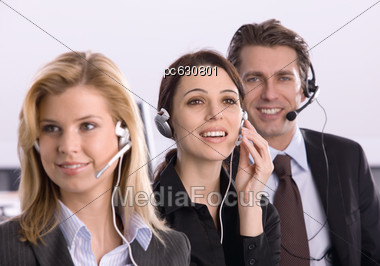 Two Women And Man With A Headset In The Office Stock Photo