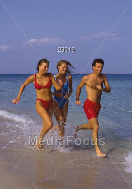 Two women and a man running along the beach Stock Photo