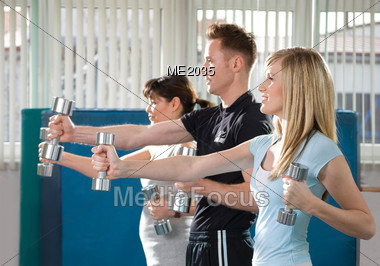 Two Women & Man Training With Dumbbells Stock Photo