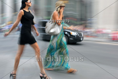 Two Women Walking On A City Street In Motion Blur, One Of Them Using On A Mobile Phone Stock Photo