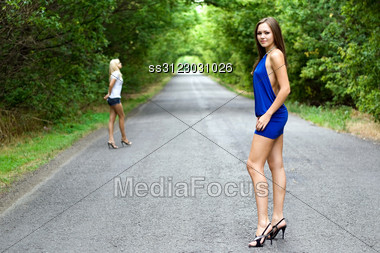 Two Women Walking On The Road. Focus On Brunette Stock Photo