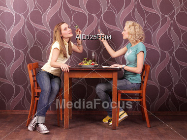 Royalty Free Stock Photo: Two Young Women Sitting At Table In A Bistro,  Photographed With Mobile Phones