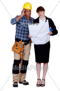 Unhappy And Puzzled Tradesman And Engineer Looking At A Blueprint Stock Photo