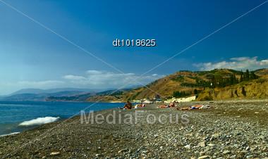 Unrecognizible People On The Black Sea Beach Stock Photo