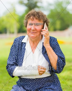 Up To Date Grandmother With Plaster Chatting With Family Mambers On Her Smartphone Stock Photo