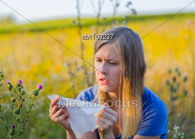 Upset Adult Woman Blowing Her Nose Because Of Ragweed Allergy Stock Photo