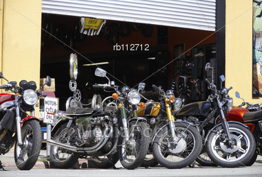 Various Motorbikes Parked At The Curb Outside A Workshop Garage Stock Photo