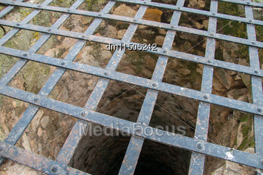 Very Deep Old Water Well With Grid Stock Photo