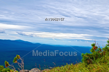 View Of The Chain Of Mountain Peaks Of The Northern Urals (Kosva), Sky And Clouds, Green Grass And Small Trees Cedar Stock Photo