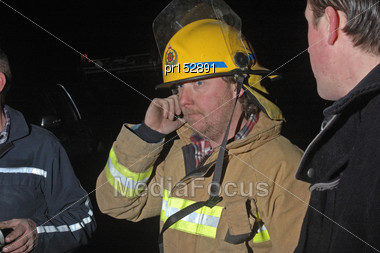 Volunteer Fire Fighter Relays Messages On A Mobile Phone During An Evening Bushfire, Westland, New Zealand Stock Photo