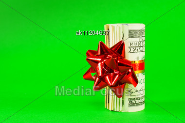 Wad Of US One Hundred Dollar Bills Tied Up With Red Ribbon Over Green Background Stock Photo
