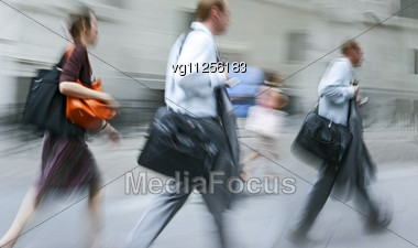 Walking Business People Rushing On The Street In Intentional Motion Blur Using A Mobile Phones Stock Photo