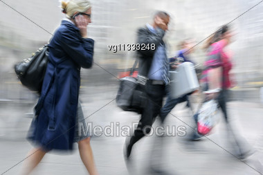 Walking Business People Rushing On The Street In Intentional Motion Blur,both Using Mobile Phones,couple Walking In The Background Stock Photo