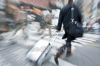 Walking Businessman Rushing Across The Street In Intentional Motion Blur Carrying Luggage Cart Stock Photo