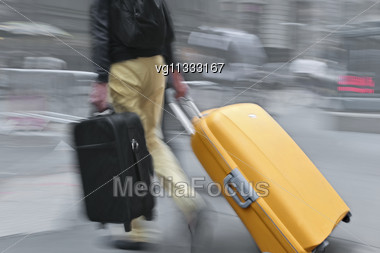 Walking Businessman Rushing Across The Street In Intentional Motion Blur Carrying Luggage Carts Stock Photo