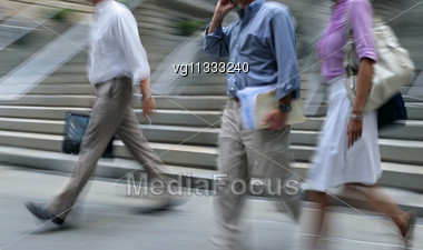 Walking Businessman Rushing On The Street In Intentional Motion Blur Using A Mobile Phone, Two Persons Walking By Stock Photo