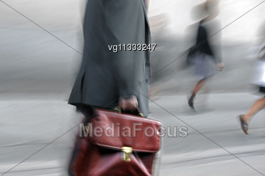 Walking Businessman Rushing On The Street In Intentional Motion Blur Stock Photo