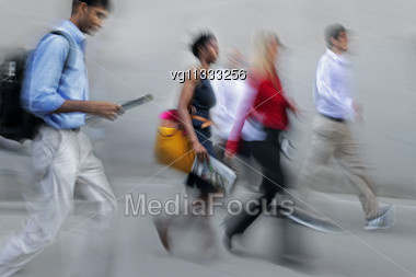 Walking Businessmen And Businesswomen Rushing On The Street In Intentional Motion Blur Stock Photo