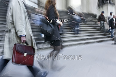 Walking Businessmen Rushing On The Street In Intentional Motion Blur Holding Briefcase , Young Woman Passing By Stock Photo