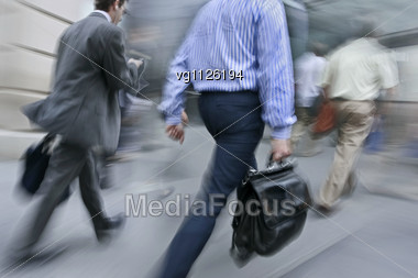 Walking Businessmen Rushing On The Street In Intentional Motion Blur, One Of Them Using A Mobile Phone Stock Photo