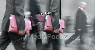 Walking Businessmen Rushing On The Street In Intentional Motion Blur Carrying Folders Stock Photo