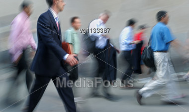 Walking Businessmen Rushing On The Street In Intentional Motion Blur Carrying Bags And Briefcases Stock Photo