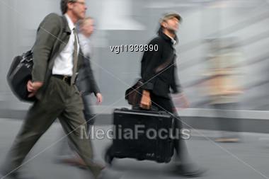 Walking Businessmen Walking On The Street In Intentional Motion Blur Stock Photo