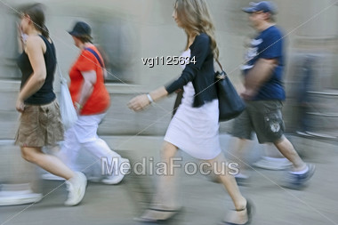 Walking Man And A Women Rushing On The Street In Intentional Motion Blur Holding Bags Stock Photo