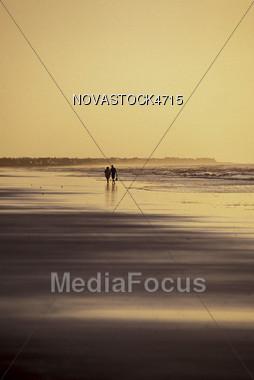Walking on Beach at Sunset Stock Photo