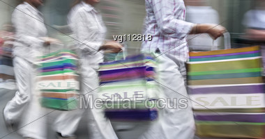 Walking Women Rushing On The Street In Intentional Motion Blur Carrying A Shopping Bags With Words Sale Stock Photo