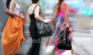 Walking Women Wearing Color Dresses Rushing On The Sidewalk At Hot Summer Day Stock Photo