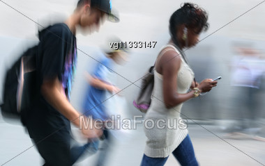 Walking Young People Rushing On The Street In Intentional Motion Blur, Woman Using Cell Phone And Mp3 Player Stock Photo