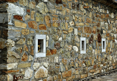 Wall Of An Old Stone Church With Three Small Marble Window Stock Photo
