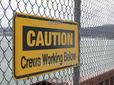 Warning Signage Hanging From A Wire Fence Stock Photo