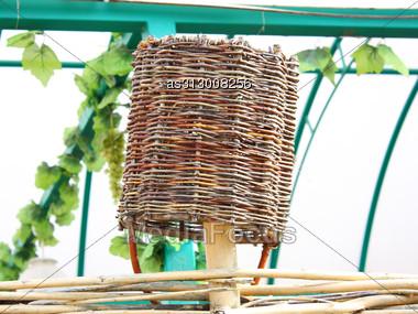 Wattled Basket Hangs On A Wattled Fence Upside Down Stock Photo