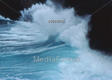 Wave Breaking On Rocks Stock Photo