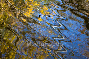 Wavy Reflections Of Autumn Colors In The Water Stock Photo